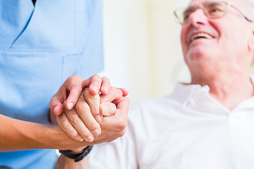 Nurse holding hand of a senior man in a rest home