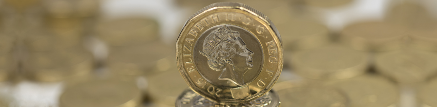 New British £1 coin on pile of old £1 coins.