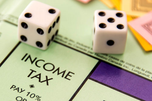 A pair of dice lying on the Income Tax square of a Monopoly board
