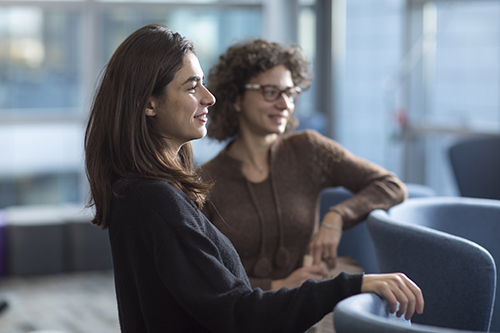 Two female finance PhD students in meeting. Both are listening and smiling at something.