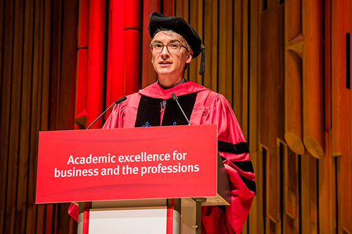 Professor Paolo Volpin stands behind a lectern in red academic robes