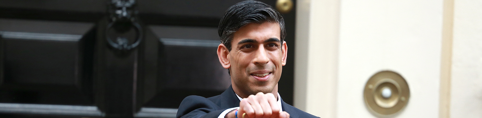 Rishi Sunak stands outside 11 Downing Street holding a red box on Budget Day