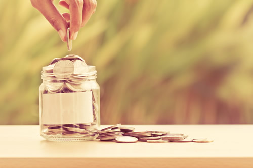 A hand adding coins to a jar