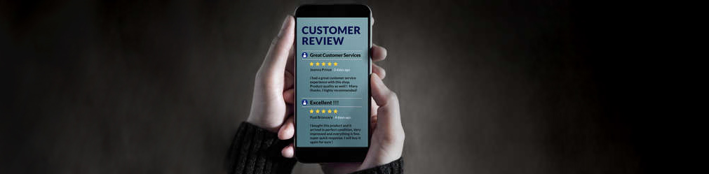 Hands holding a phone containing online reviews