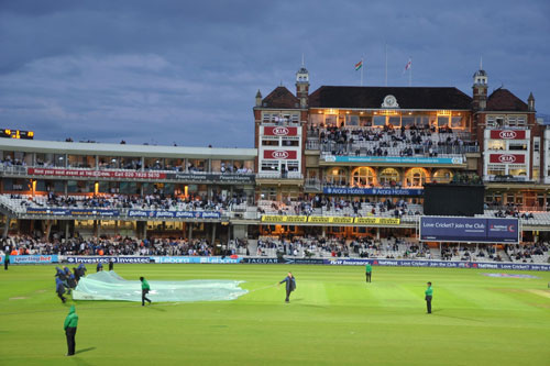 Oval staff pull the covers over a cricket pitch during a rain interrupted match.