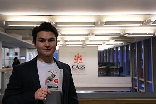 man standing in front of cass business school logo