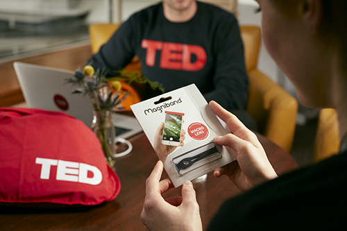 the back of a man holding a magniband, with the body of somebody wearing a TED t-shirt in the background