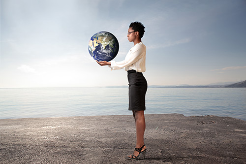 Black businesswoman holding the world in her hands.