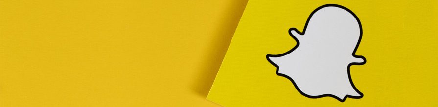 Snapchat logo on yellow paper.