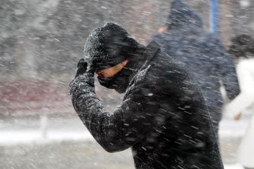 A man walks through a wild snowstorm holding a scarf to his face.