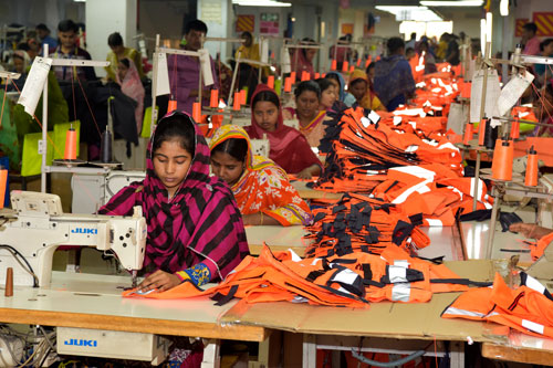 Female garment factory workers sit at rows of sewing machines surrounded by clothes in a large room