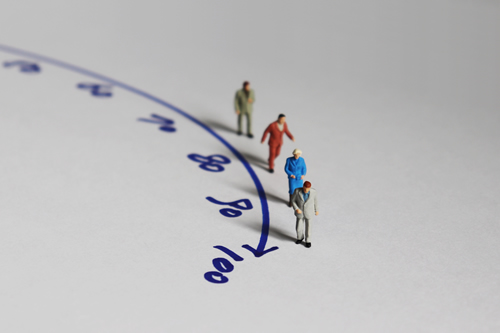 Aged miniature figures moving along a timeline