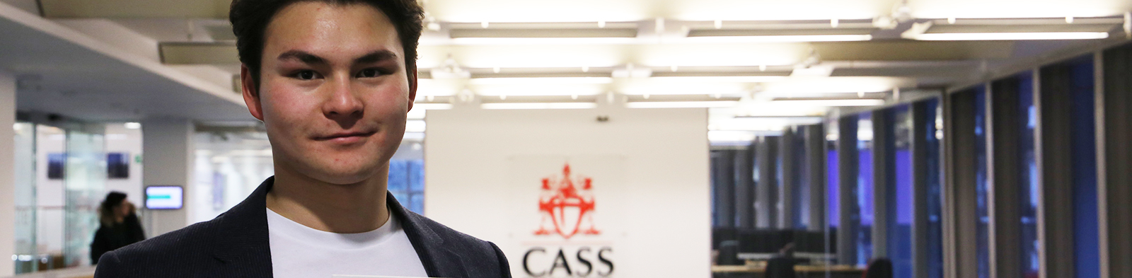 man standing in front of cass business school logo