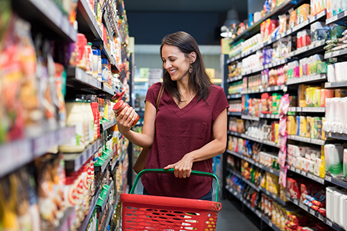 Woman carrying a shopping basket looking at items in the aisle of a supermarket