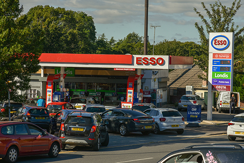 Cars queuing at a petrol station along the road