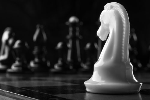 A white rook chess piece faces across the board to a row of opposing black pieces.