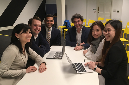 students and clients sitting around a table smiling