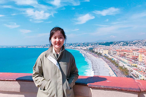Yiqi Chang in front of a beach