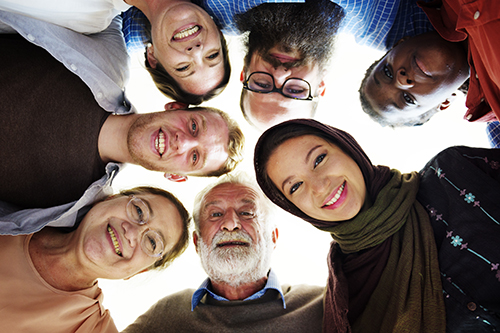A group of people with different backgrounds and ethnicities smile together