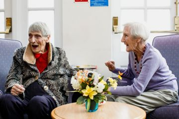 Two elderly ladies (Joyce Webb and Beryl Fox) laughing together at Whiteley Village.