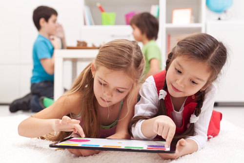 Little girls playing on a tablet computing device laying on the floor