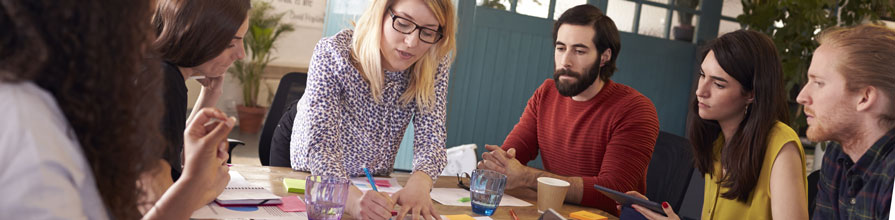 A female speaker leads a small group of professionals through a workshop around a table.