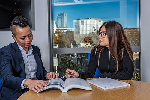 Two PhD students sitting at a table with a large window behind them with a blue sky view, discussing the contents of a book.