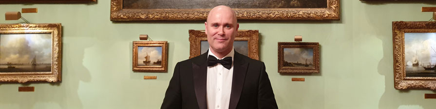 A man dressed in a tuxedo and black bowtie holds a silver plate in front of a lavishly decorated wall.