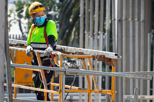 worker on building site with hi-vis jacket and face mask
