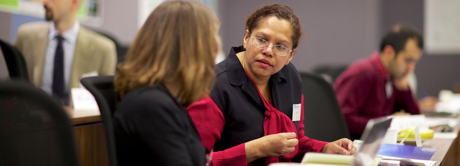 Two women speaking in a seminar