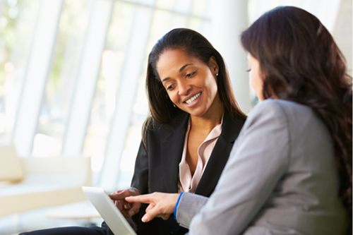 Two women in a business meeting looking at a laptop