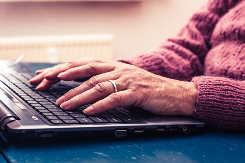Old person typing on a laptop