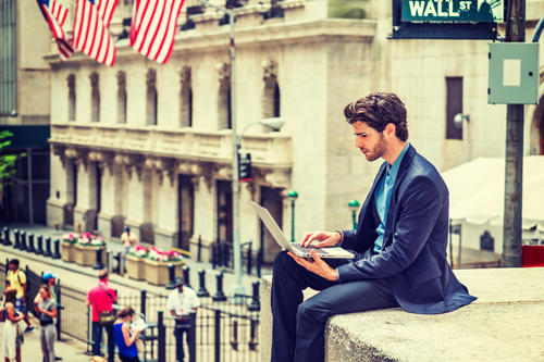 Young man in suit sitting on wall with laptop in New York. Business leaders social media