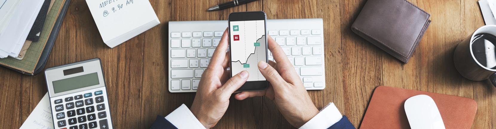 Man looking at pensions graph on phone at desk