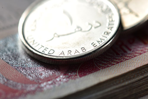 An extreme close up of a one dirham UAE coin atop a nondescript UAE banknote.