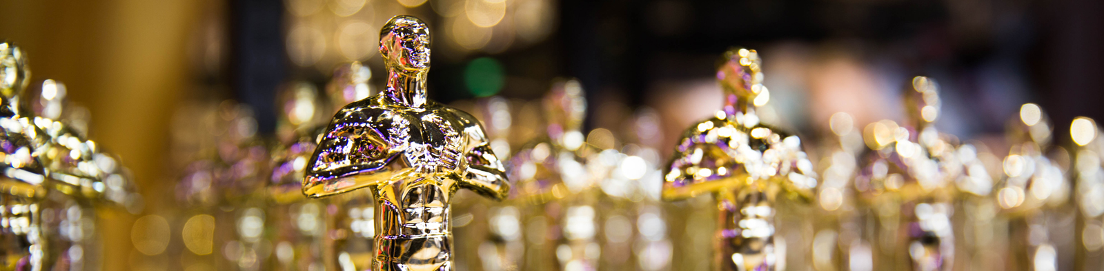 A line up of shining gold Oscars award statues.
