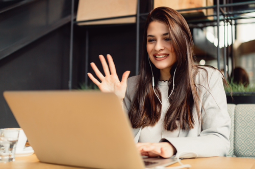 woman smiling into a video conference call on laptop