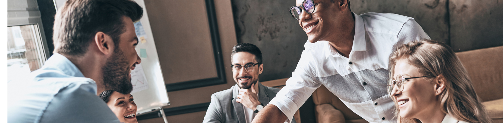 Smiling colleagues shaking hands in a boardroom