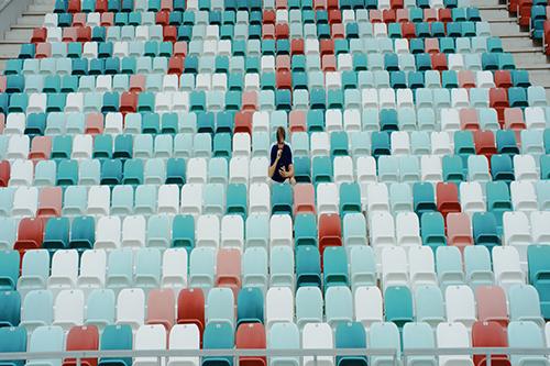 A single fan sits in an empty stadium