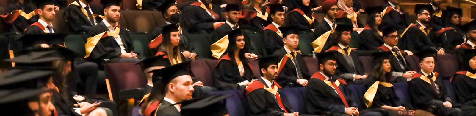 Professor Caroline Wiertz standing behind a lectern in graduation gown and hat
