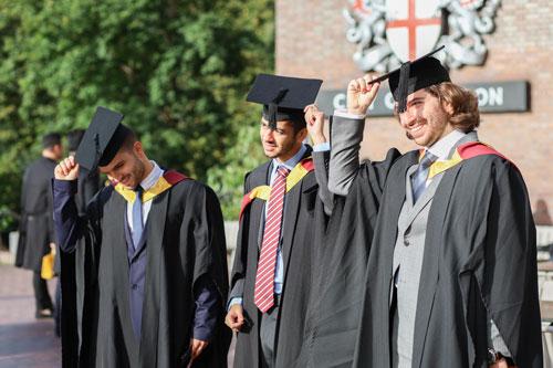 Three male Bayes graduates doff their caps