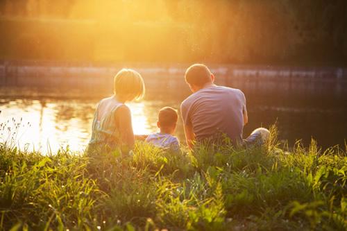 A family sat by a lake