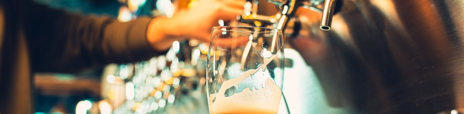 A young bartender pours beer from a tap into a glass in a busy bar.