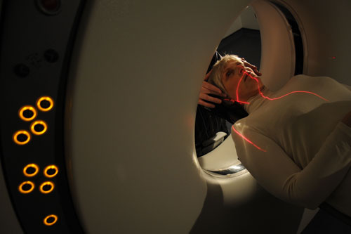 A woman lies in a CT scanner.