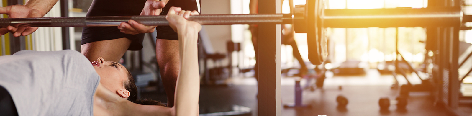 A woman benchpresses in the gym
