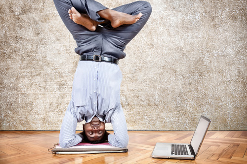 Man doing handstand and looking towards his laptop. Flexible working.