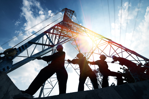 Silhouettes of men working on electricity pylon.
