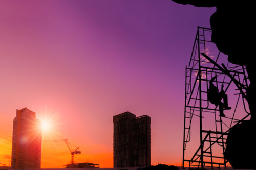 Silhouette of worker climbing scaffolding on high buildings construction