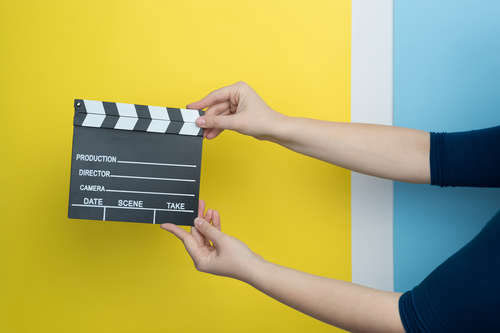 Female hands holding a film clapperboard on yellow and blue background