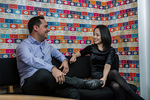 Two PhD students, one male, one female, sitting on a sofa in the School and talking casually. Behind them the wall is covered with a wallpaper pattern of old penguin book covers.